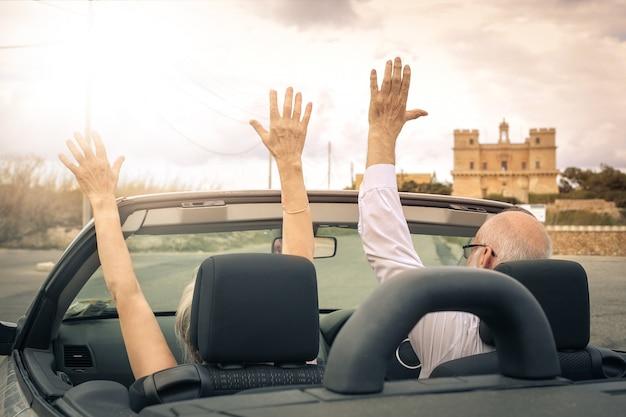 Пожилая пара за рулем кабриолета