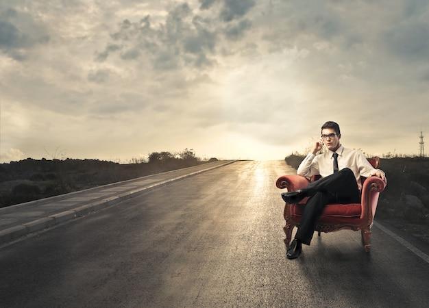 Бизнесмен сидит в кресле на дороге