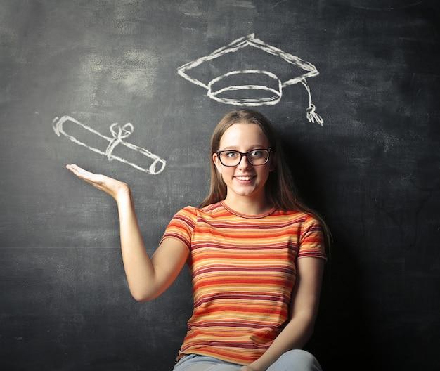 卒業証書を持っていることに熱心な若い女性