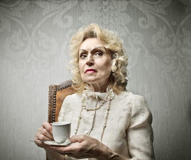 一杯のコーヒーを飲んでいる年配の女性