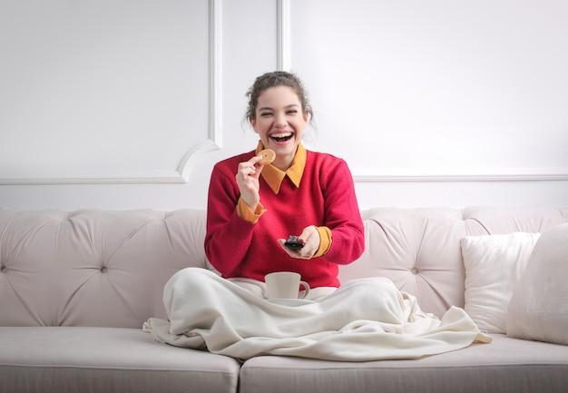 Счастливая девушка смотрит телевизор у себя дома