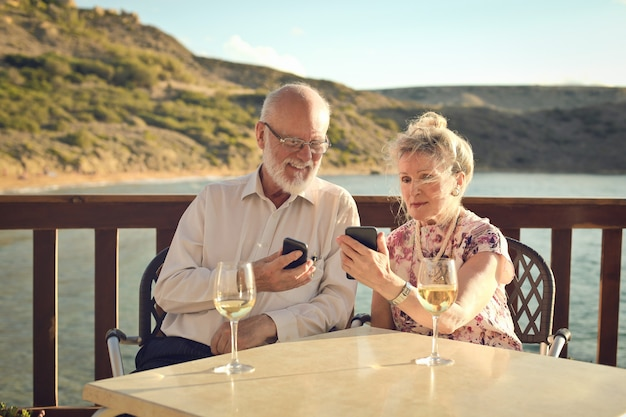 年配のカップルが休暇にスマートフォンを使用して