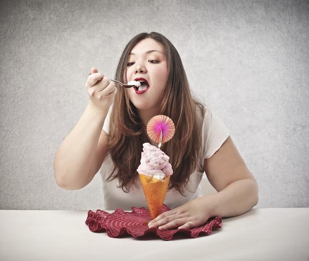 アイスクリームを食べる太った女性