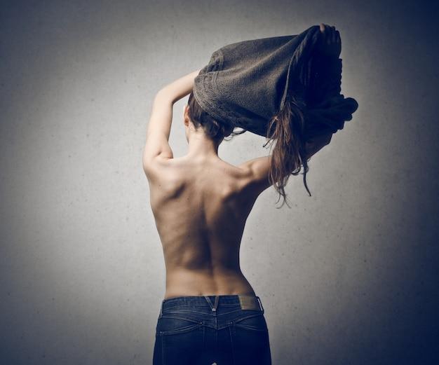 美しい女性が彼女の服を脱いで