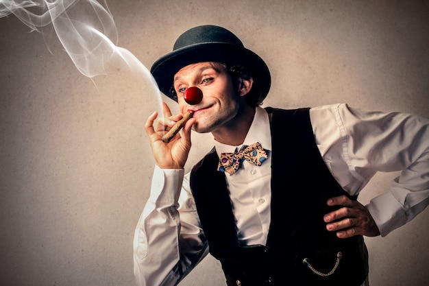 Смешной клоун курит сигару