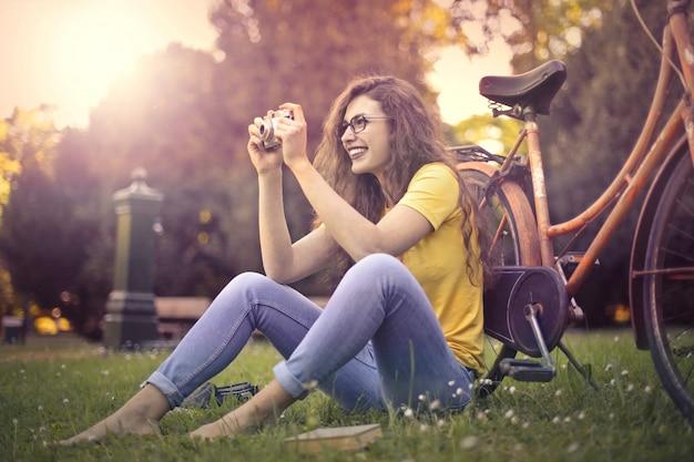 女性はビンテージカメラで写真を撮る