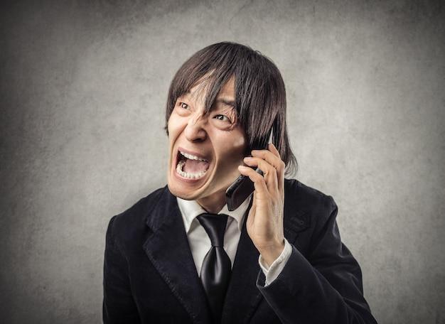 電話で叫ぶ日本人男性