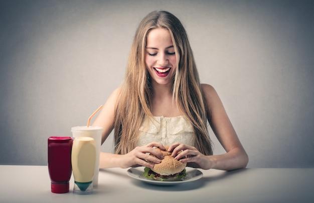 ハンバーガーを食べて幸せなブロンドの女の子