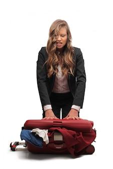 怒っている女性が彼女のスーツケースをパッケージ化