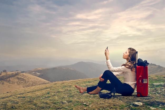 旅行で通信しようとする若い女性