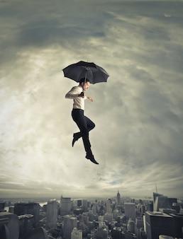 傘で飛んでいる男