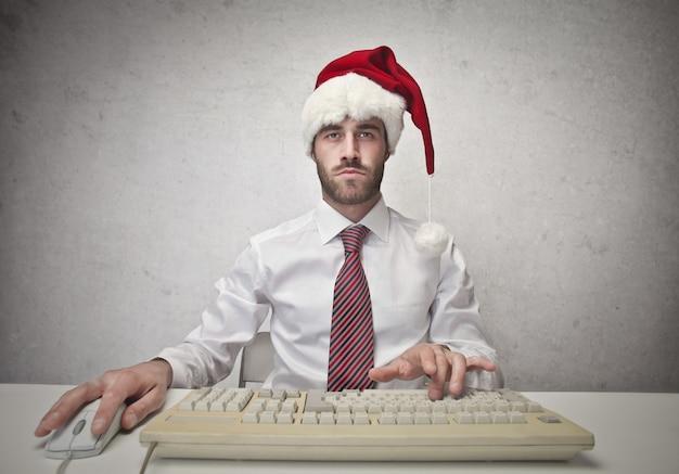 サンタの帽子を着ているビジネスマン