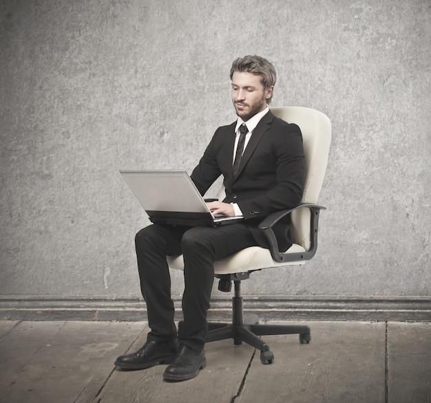 Элегантный бизнесмен сидит в кресле с ноутбуком