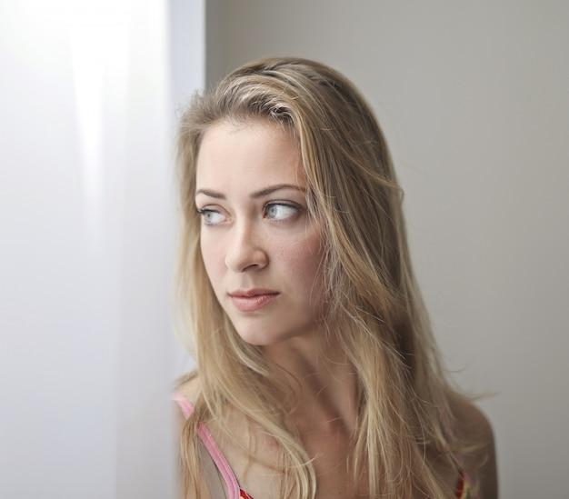 窓の外を見て金髪の女性