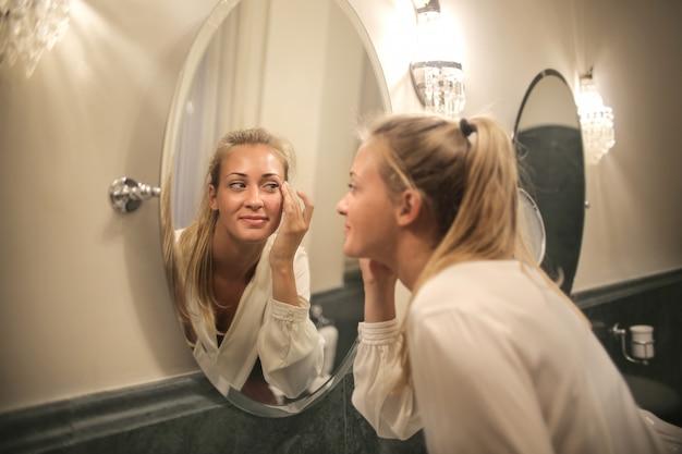 金髪の女性が鏡で自分自身をチェック