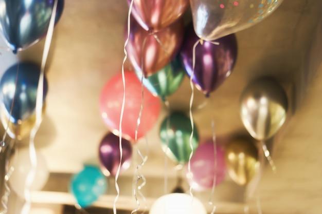 天井の下の色とりどりの風船で背景をぼかした写真。お祝いのコンセプトです。
