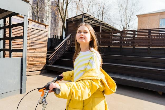 黄色のスウェットシャツとスクーターで都市景観の黄色のジャケットの美しい十代の少女。