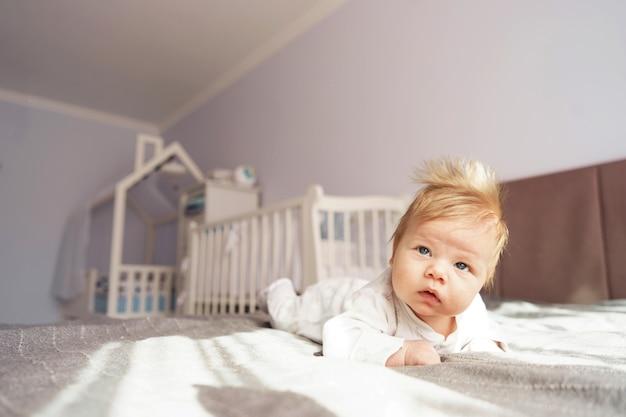 生まれたばかりの赤ちゃんは、ベッドの上の保育園でお腹の上に横たわっています。