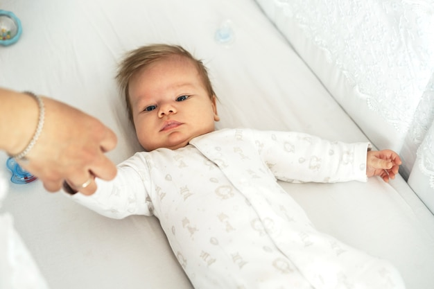 生まれたばかりの赤ちゃんがベッドの上の保育園に横たわっています。