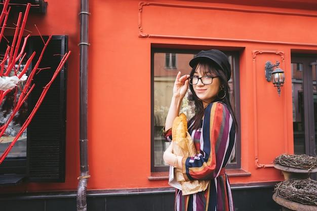 人工的なインストールで赤い壁に明るいドレスを着た若い長い髪のブルネットの女性