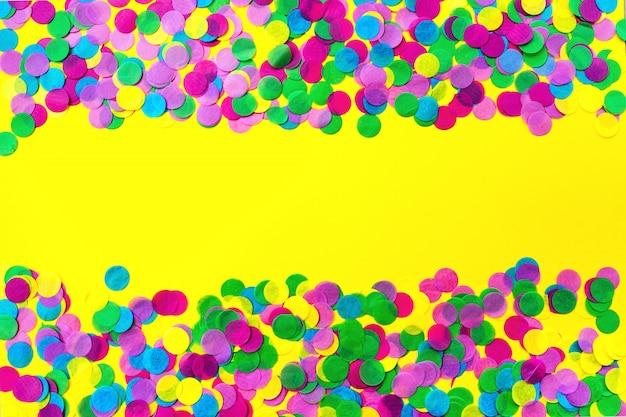 黄色の背景、お祭りのコンセプトに色とりどりの紙吹雪