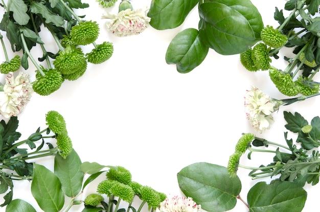 Композиция цветов. рама изготовлена из цветов и листьев на белом фоне.