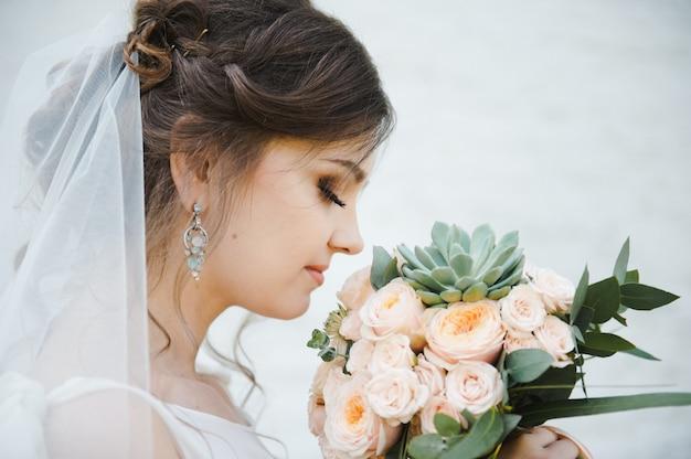白い背景の上の花束を持つ美しい若い花嫁の肖像画。結婚式。