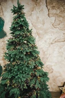 Рождественская елка с гирляндами. рождественская елка с игрушками на коричневом фоне ретро стены