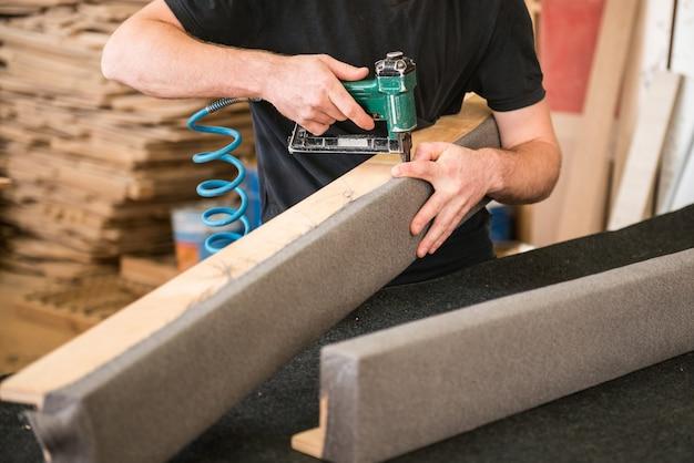 Изготовление деревянной мебели. человек-плотник в серой футболке и работающий в целом равняется деревянному брусу с фрезерным станком в мастерской, на заднем плане деревянные доски.