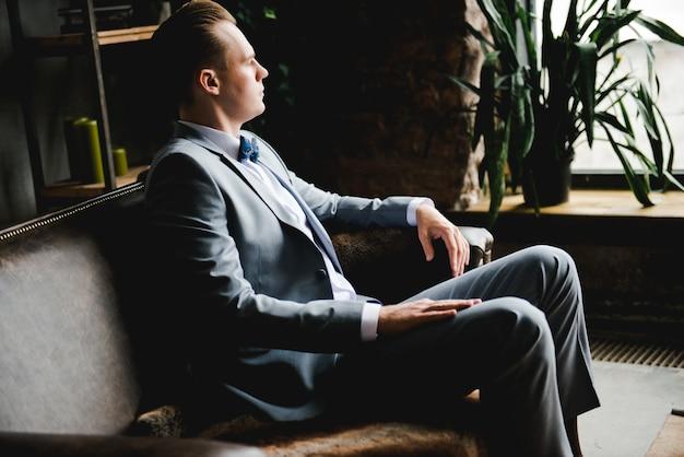 Портрет мужчины. жених в сером костюме, белой рубашке и галстуке-бабочке сидит на коричневом кожаном диване.