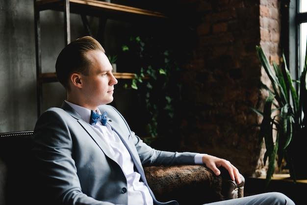Жених в сером костюме, белой рубашке и галстуке-бабочке сидит на коричневом кожаном диване.