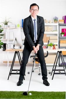 黒のスーツで若いアジア系のビジネスマンはオフィスでゴルフを練習しています。