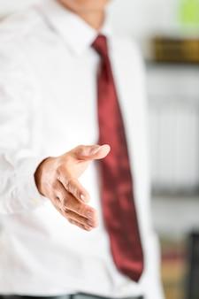 ビジネスの男性は握手をする準備ができている手を開きます。
