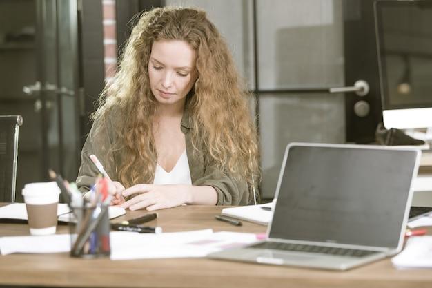 カジュアルなオフィスで白人女性。
