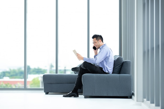 オフィスで携帯電話を使用するビジネスマン。