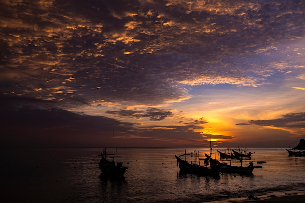 Утренний морской пейзаж с силуэтом лодок и красивым небом