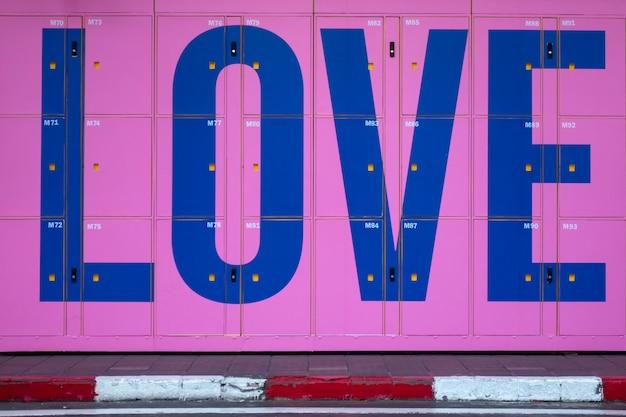 Розовый шкафчик с любовью на пешеходной дорожке рядом с улицей.
