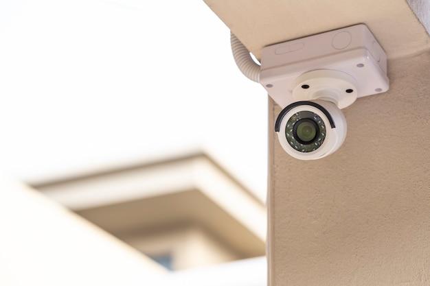 Видеонаблюдение на столбе дома на белом фоне