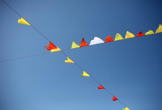 ストリートフェスティバル、フェア、または青い空を背景にパーティーのカラフルな国旗