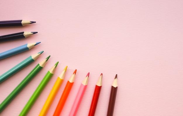 Разноцветные карандаши радужных цветов на розовой пастели