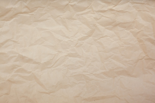 淡い茶色のしわくちゃの紙のテクスチャ背景。
