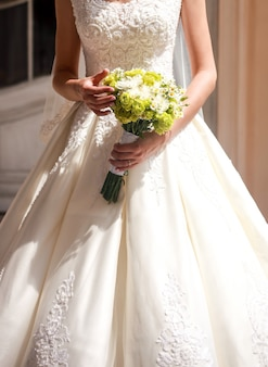 太陽の下で花の美しい結婚式の束を保持している花嫁