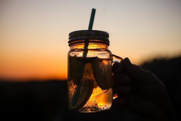 夏の屋外のピクニック、レモネード、暖かい日光の下で格子縞の夏の飲み物瓶