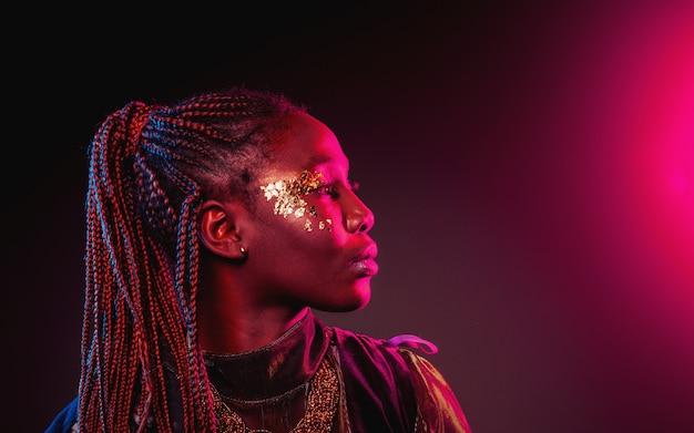 アフロの髪型と金色の光沢のある化粧の若いアフリカ人女性。スタジオ撮影。青とピンクのネオンライトフレア。