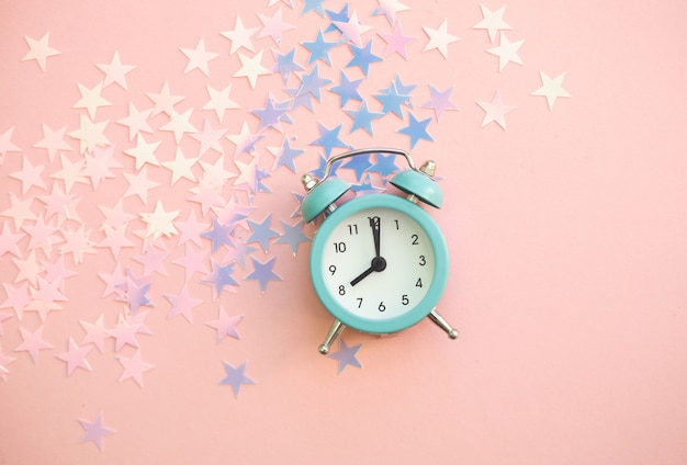 星の光沢のある紙吹雪とビンテージの目覚まし時計