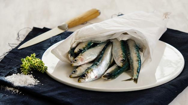 Свежие сырые сардины с солью и зеленью на белой тарелке