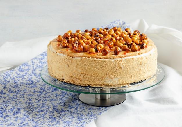 Торт с муссом, карамелизированными яблоками, украшенный лесным орехом в карамели