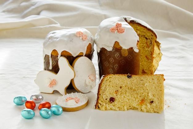 伝統的なイースター、甘いパン装飾メレンゲと皿の上の青いキャンディー杖形卵