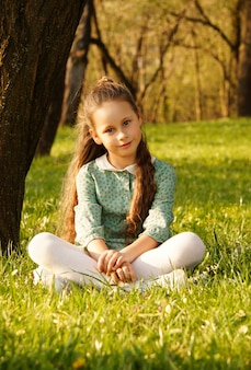 草の上の公園に座って、美しい若い笑顔の女児