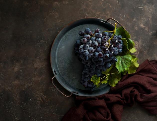 Темная гроздь винограда с каплями воды при слабом освещении, красное вино, темное фото с копией пространства